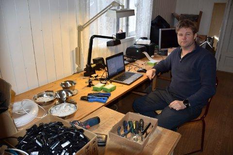 PRODUKSJONSLINJE: Ved bordene som tidligere ble brukt når det ble servert kaffe fra misjonskjelen er det produksjonslinje. – Her monteres de grønne boksene som skal sørge for kommunikasjon mellom skogsentreprenør og tømmerkjøpere, sier Isak Hasselvold.