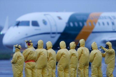 SMITTSOMT: Soldater i vernedrakter venter på evakuerte brasilianere fra byen Wuhan i Kina. Bildet er tatt 9. februar ved Annapolis flybase i staten Goias i Brasil.