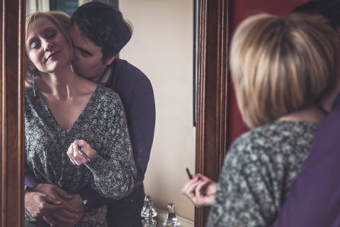 Husband kisses his wife on the neck while she's making up for a party, intimacy and closeness