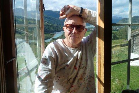Ute eller inn: Det er ikke godt å si om Kjell Erik Killi Olsen ser ut på eller inn i verden fra Sandbu, hans nye hjem i Vågå. Men her ser han helt klart inn gjennom kjøkkenvinduet, med et lite smil om munnen. Det kan være fordi han er tilbudt to kalver som kan beite den bratte bakken utenfor vinduet. Killi Olsen føler seg velkommen i Vågå. Det er en god begynnelse på noe nytt for Norges mest meriterte samtidskunstner internasjonalt.