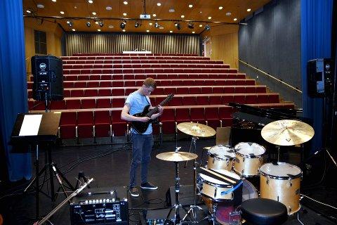 Gjør seg klart til eksamen: Elias Solberg Skjellum fra Otta i minuttene før eksamen i hovedinstrumentet gitar. – Jeg kjenner det fysisk. Så nervøs er jeg, sier han. Bruker de siste minuttene på å finpusse låtene. Og så slippes publikum inn.
