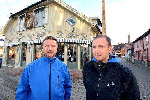 Bjønne Owren (t.h.) og Per Erik Lykstad foran trehuskvartalet som strekker seg fra Storgata og langs Elvegata. (Klesforretningen Fjøs holder nå til i lokalene der Spot var tidligere.)