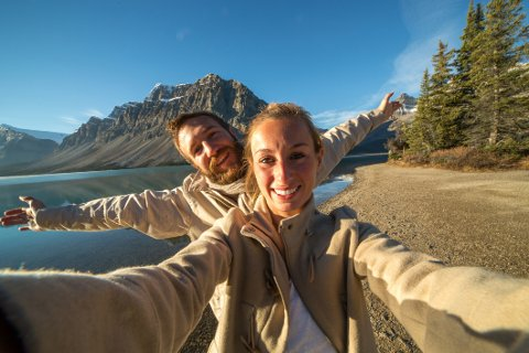 Young couple by the lake taking a selfie portrait. Sun rising on the mountain peaks.