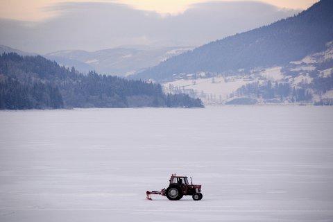 BRØYTING: Trond Bjerkestuen bruker traktor for å brøyte isbanen på Losnavatnet. Onsdag gikk han gjennom isen.