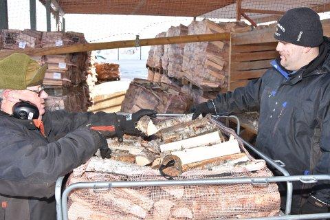 PAKKER: Bjørn og Brede er allerede igang med å å pakke neste års ved i storsekk.