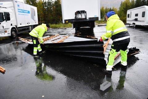 Einar Eiasar og Kjell Rusten i gang med å rydde opp takplatene som natt til onsdag i stormkast rammet parkerte  vogntog i Skjåk.