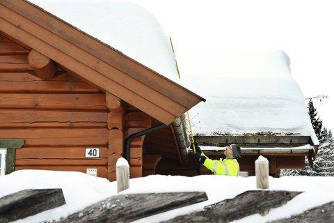 INGEN FARE: Einar Einstad målte snødybden på taket til 1,2 meter torsdag. – Det er ikke noe problem for nyere hytter som er dimensjonert for mer enn det dobbelte, sier han.