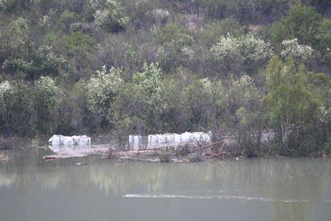 Mange store sekker med Glasopor lå onsdag i vannet  ved Risheimsøya i Skjåk. Nå er de fraktet ut med helikopter