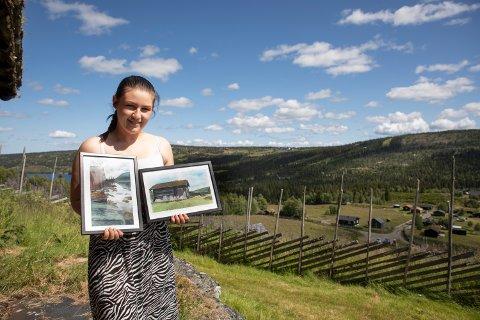 Kristina Solbraa Grytting (22) viser frem to av maleriene hun har malt. I bakgrunnen er det ene stabburet, og til høyre for bildet ligger vannet der naustet hun har malt står.