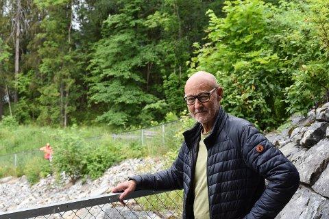 Vidar Hanssen har vokst opp i traktene til Årettadalen. Her står han ved sikringsgjerdet som sier at veien har stoppet. Bak ham går veien ned fra jernbanen til Mjøsa. Foto: Hanna Willoch.