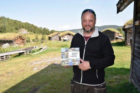 Øistein Formo med beviset på at Vågåfjell Turløyper As sitt arbeid er hedret, og omtalt i bok.