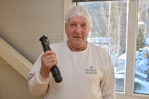 Slakter Arild Aamodt viser frem boltepistolen han kom i skade for å skyte seg selv med. Piggen, eller bolten, som skytes ut er 15 centimeter lang.