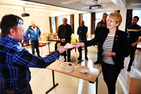 Ordfører i Sel, Eldri Siem fikk æren av å skjære første stykket av festkaka på regionkontoret fredag. Her med styreleder i Gudbrandsdal Slakteri, Terje Jonny Sveen. Medlemmer av produsentgruppa i bakgrunnen.