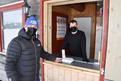 MAT GJENNOM LUKA: Gjestene på spisestedet i alpinbakken i Natrudstilen får kun komme inn for å bestille. Deretter blir maten delt ut gjennom ei luke i veggen når den er klar. Fra venstre: Erik Lindstad og Lukas Juodziukynas.