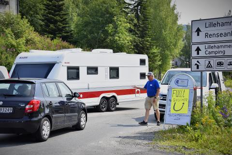 Det blir trangt når campingvogner og bobiler må snu foran en full campingplass. Her står camping-sjefen og dirigerer trafikk.