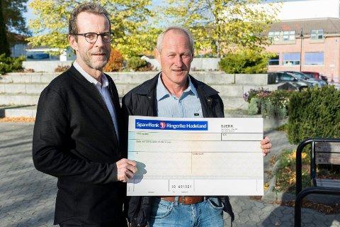 GIR GAVER: Denne sjekken har ikke noen mottaker ennå. Men Bjørn Haugen Morstad og Lars Torgeir Dahl i Sparebankstiftelsen Jevnaker Lunner Nittedal vil gjerne ha flere søknader om pengestøtte.