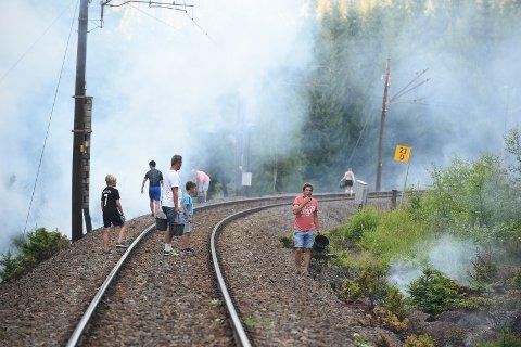 SLUKKING: Her er lokalbefolkningen i full gang med å slukke småbrannene langs jernbanelinja.