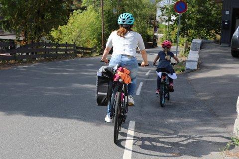 TRYGT: Hvis det ikke er adskilt sykkelfelt langs vegen, er det lurt å legge seg litt bak og på utsiden av barnet. Da skjermer du barnet mot biler som kommer bakfra.