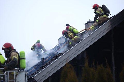 Omfattende: Brannvesenet jobber med å slukke brannen som også har spredt seg i taket.