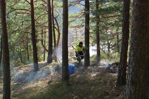 ULMEBRANN: Her slukker Halden brannvesen ulmebrannen.