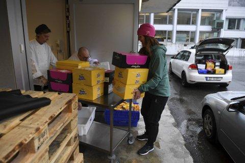 Olaug Tveiterås Lid fra Travel Retail Norway overleverer kassevis med påskesnop til de ansatte på Bergen Røde Kors sykehjem.