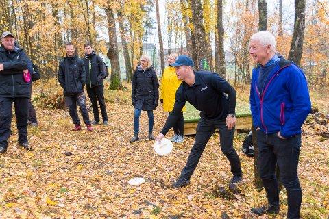 KAST: Håkon Kveseth tester det nye frisbeegolf-anlegget i Børstadlunden. Til høyre står ordfører Einar Busterud.