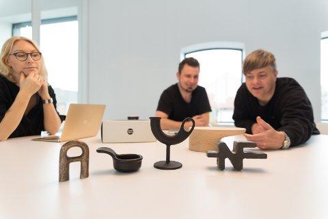 PRODUKTER: Ellen Østmoen, Jens Haugen og Kjetil Wold foran Nedre Foss-produktene. Til høyre står Nedre Foss-logoen i støpejern.
