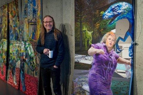 ERNA PÅ VEGGEN: Inge Iversen er i ferd med å montere sitt verk, der Erna Solberg er i ferd med å ta et mageplask blant øgler og dinosaurer.