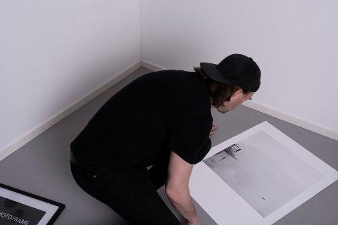 UTSTILLING: Eirik Jeistad i ferd med å montere bilder som skal være med i utstillingen «Stupetårnet».