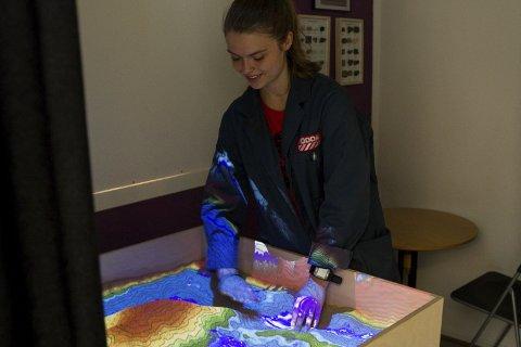 Eirun Flaten Sandvin viser fram KraftLaben sin nye hovudattraksjon, ei sandkasse der ein kan forme sand til landskap som på eit 3D-kart