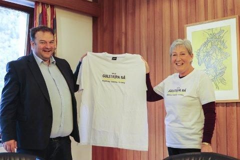 T-skjorte: Liv Eikemo Opdal overrekte ei t-skjorte til ordføraren med teksten Rv. 13 Gulstripa Nå. Arbeidsveg. Skuleveg. Turistveg.