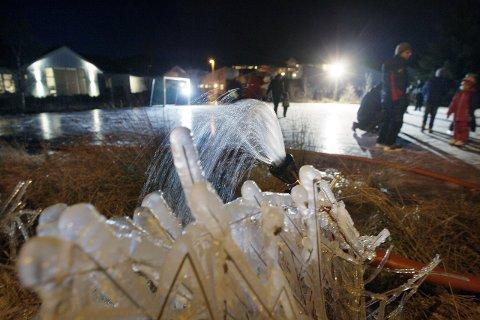 GJØRE TING SAMMEN: Velforeningen på Stemmemyr sprøytet fotballbanen med hjelp fra brannvesenet. Foto: Harald Nordbakken