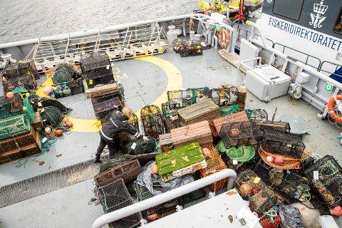 Inspektør fra Fiskeridirektoratet sorterer beslaglagte redskap fra dag 3 på akterdekket på KV Tor.