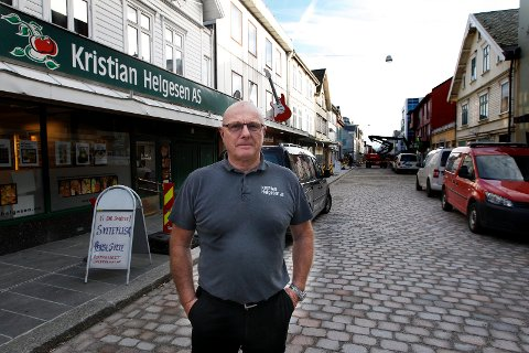 SELGER: Kjell Helgesen utenfor butikken nord i Haraldsgata, som han dreiv i mange år. Bildet er tatt i 2018, før oppgraderingen av gata var ferdig. Han solgte butikken året etter, og nå selger familien huset også.