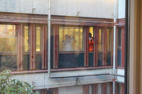 BILDE: Ansatte samlet seg i vinduene som vender ut mot atriet der maskinen ble løftet ned.
