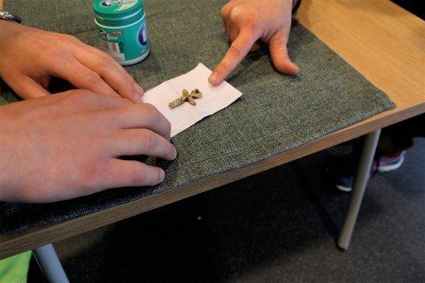 LITE: Arkeolog Christopher Kvæstad forklarer at det var vanlig med mindre blykors, på grunn av vekten til blyet.  Korset er 4 cm i høyden, og 3 cm i bredden.