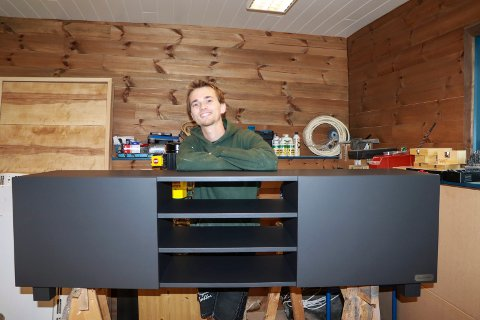 FERDIG: Møbelsnekker Jonas med en ferdig Tv-benk han har laget i heltre på mål.