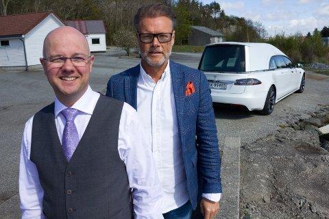 FORNØYD: Jan Erik Naley (bak) har solgt verdens første hvite Tesla bårebil, og kjøper er Jon Børge Frafjord fra IMI Tromsø. Torsdag ble bilen overlevert.