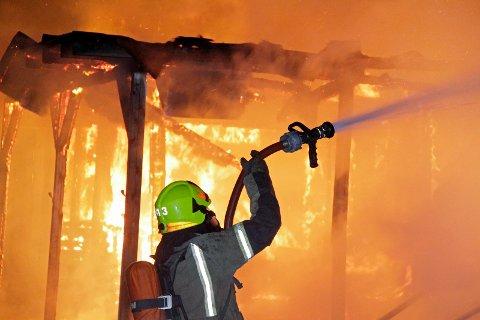 I ARBEID: Brannmann i arbeid på da det brant på Helganes motorsportsenter i 2014.