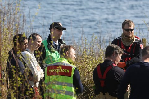 VET HVEM AVDØDE ER: Politiets innsatsleder Tore-Frøyland Jensen (bak med caps) og brannvesenets mannskaper på stedet.