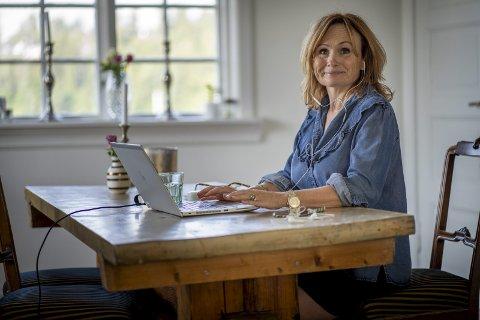 I STUA: Wenche Sætersdal i Telenor synes det går fint å jobbe hjemmefra, selv om hun setter pris på de dagene hun er på kontoret. Her sitter hun i spisestua si, hvor hun ofte sitter når hun har hjemmekontor. Foto: NTB
