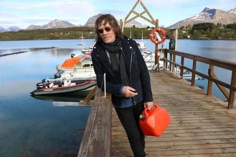 """En havets mann. Hugo Aasjord ved småbåthavna på Engeløya. Bak til venstre ligger den berømte rib'en fra """"Havboka""""."""