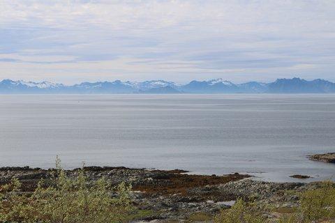 På den andre sida av Vestfjorden skiller ei mørk hvelving seg ut fra Lofotveggen i bakgrunnen. Det er Skrova.