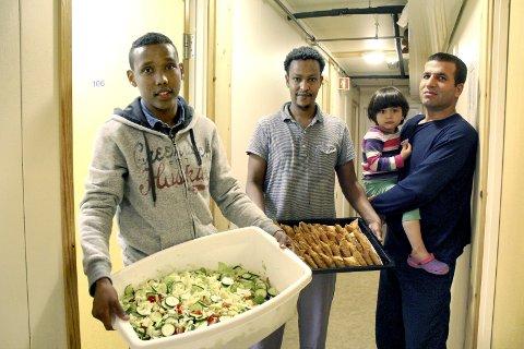 Mye mat: Beboerne har laget mye mat til feiringen. Her er fra venstre Ayanle Bashir Hassan med salat, Mohammad Ali Worseme med sambosa (begge fra Somalia) og syriske Mustafa Ramadan med Mustafa Nimar (2) på armen. foto: Benedicte Wærstad