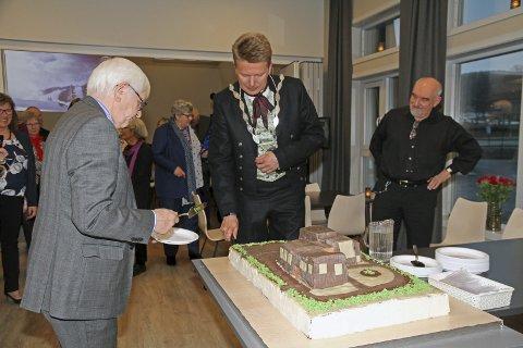 KAKEFEST: Ordfører Harald Lie skjærer det første stykket av den gedigne bløtkaka som var laget som en kopi av bygningene. Den offisielle åpningen foregikk fredag kveld. Asgeir Almås venter på serveringen.   Foto: Gunder Garsmark