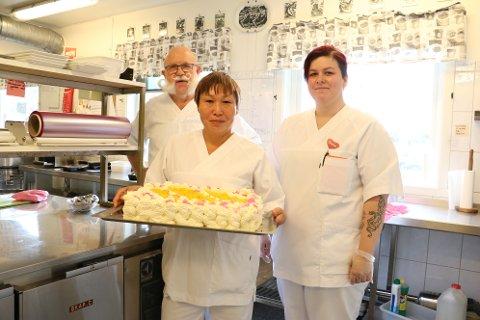Roger Eriksen, Lu Tin og Susann Wang viser fram nybakt kake som serveres til kaffen.
