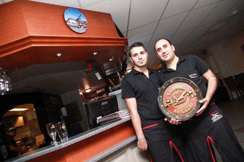 FJERNET: Yasin Erdogan (t.h.) og Mustafa Koyuncu ved Milano i Mosjøen viser  klokka som ble tatt ned fordi skjenkekontrollen bet seg merke i logoen på klokka. Over bardisken ser vi erstatningsklokka.