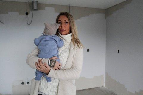 Marthe Nordås står i kjøkkenet sitt i Reinfjellveien som skule vært ferdig nå. Men innredningen lar vente på seg.