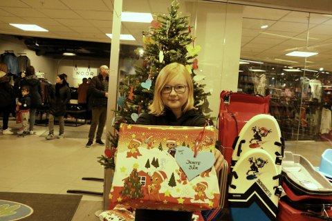 Madelen Rosenvinge Ingebrigtsen (11) har stor omtanke for andre. - Det å gjøre andre glad gjør at man blir glad selv, smiler hun foran juletreet på Ringo i Sandnessjøen. Her kan man velge ut hjerter, kjøpe gaven, og legge den under treet. 15-16 familier har så langt registrert seg.