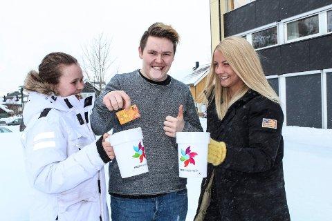 Egil Trones Christiansen demonstrerer at det også er mulig å gi med kort/vipps til bøssebærerne. Her flankert av Benedicte Kroken Kvalfors  og Ane Lundestad.